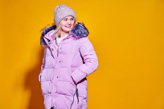 Młoda kobieta moda w krótkiej fioletowej kurtce puchowej.