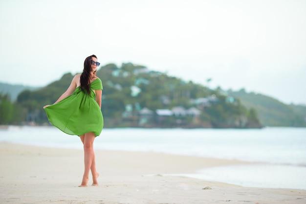 Młoda kobieta moda w zielonej sukni na plaży