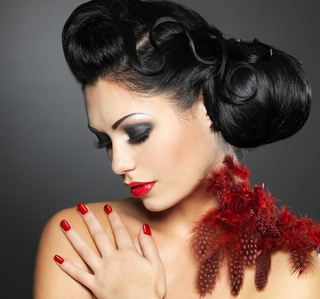 Młoda kobieta moda z czerwonymi paznokciami, kreatywną fryzurą i makijażem