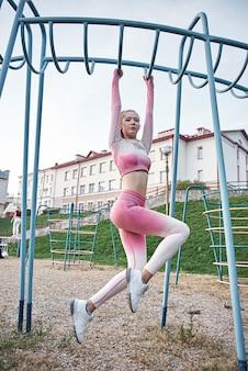 Młoda kobieta model fitness z pięknym ciałem w odzieży sportowej moda robi ćwiczenia rozciągające nogi na ulicy