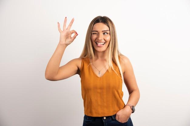 Młoda kobieta model pokazując ok gest i pozowanie.