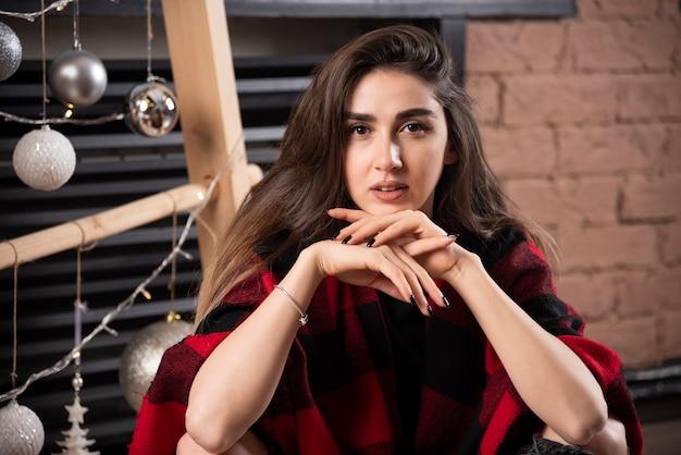 Młoda kobieta model pozowanie w kratkę w pobliżu bombek.