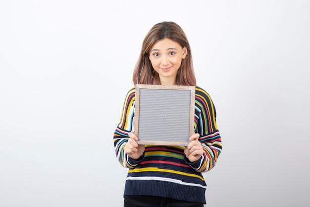 Młoda kobieta model stojąc i trzymając ramkę.