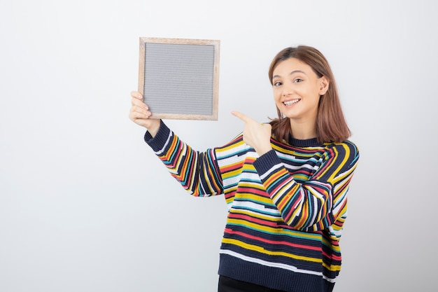 Młoda kobieta model stojąc i wskazując na ramkę.