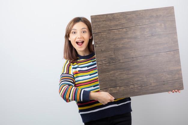 Młoda kobieta model stojący i trzymając drewniane.