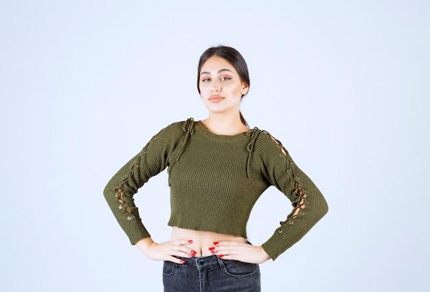 Młoda kobieta model stojący z rękami na biodrach i odwracając wzrok.