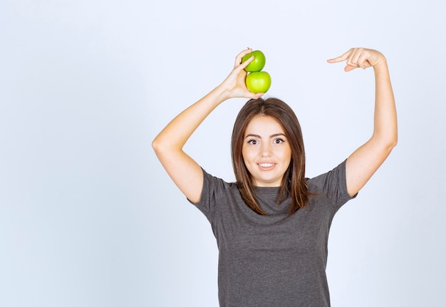 Młoda kobieta model trzyma dwa zielone jabłka nad głową i wskazując na nich.