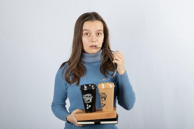 Młoda kobieta model trzyma książki i dwie filiżanki kawy.