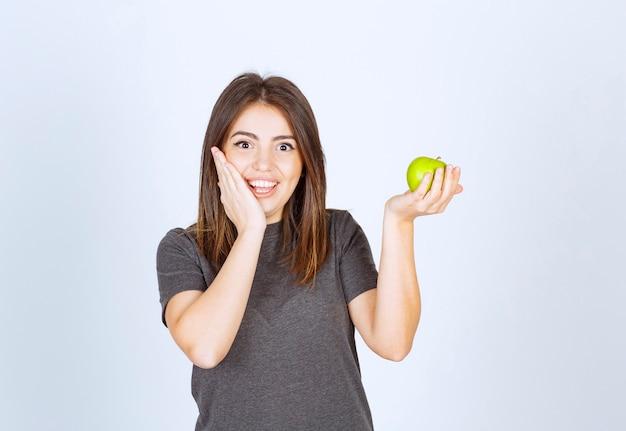 Młoda kobieta model trzyma zielone jabłko.