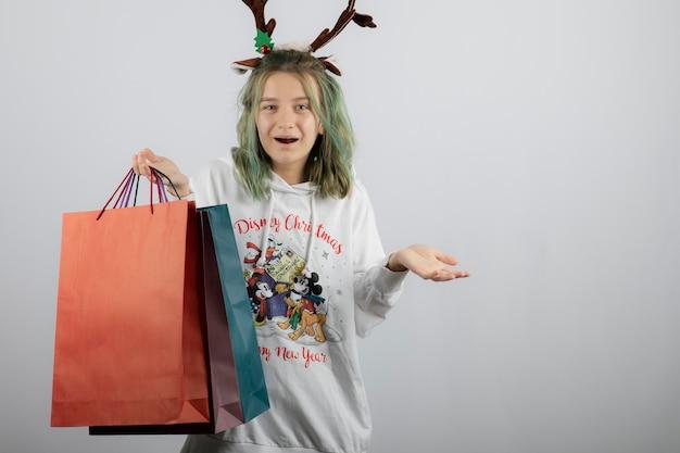 Młoda kobieta model trzymając kolorowe torby na zakupy.