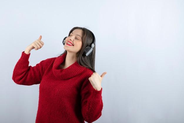 Młoda kobieta model w czerwonym swetrze ze słuchawkami pokazującymi kciuk w górę