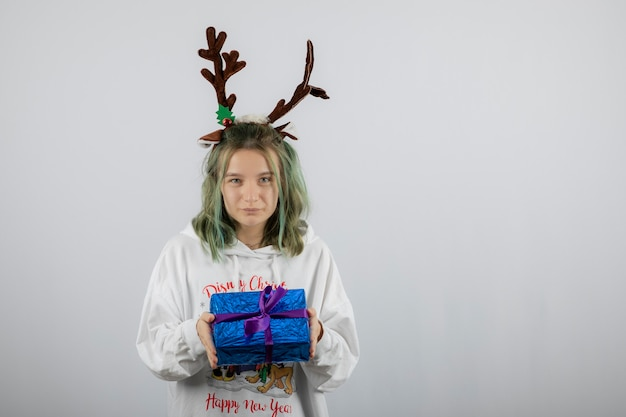 Młoda kobieta model w masce rogów jelenia trzyma prezent.