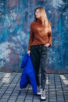 Młoda kobieta model w niebieskiej kurtce zimowej