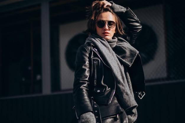 Młoda kobieta model w skórzanej kurtce na zewnątrz ulicy