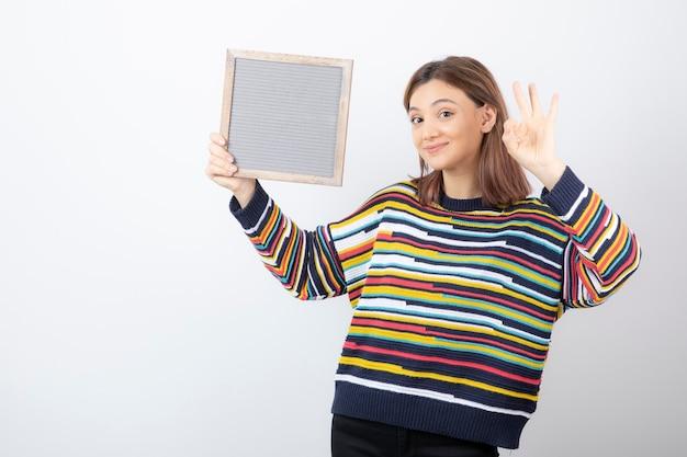 Młoda kobieta model z ramką przedstawiającą gest ok.