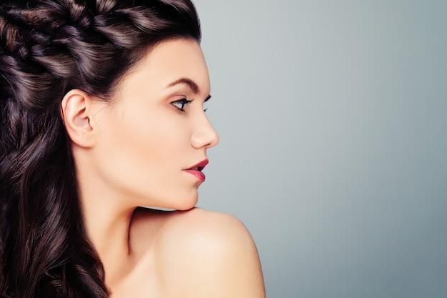 Młoda kobieta modelka. profil kobiety na niebieskim tle