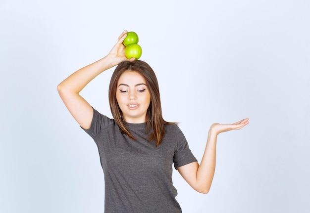 Młoda kobieta modelka trzymająca nad głową dwa zielone jabłka