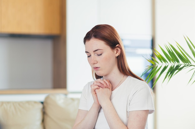 Młoda kobieta modli się szczerze z założonymi rękami w domu