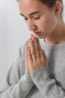Młoda kobieta modli się w domu z zamkniętymi oczami