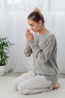 Młoda kobieta modli się w domu