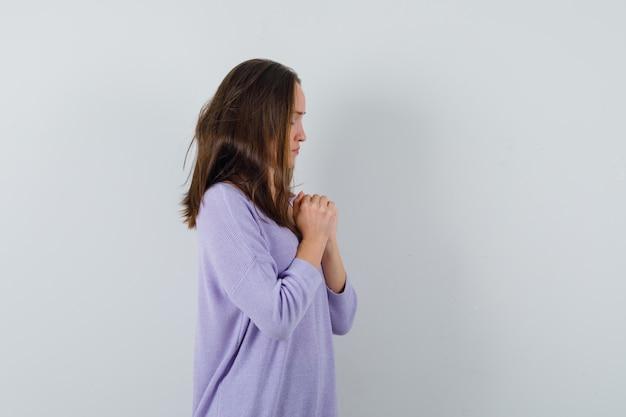 Młoda kobieta modli się w liliowej bluzce i wygląda spokojnie.