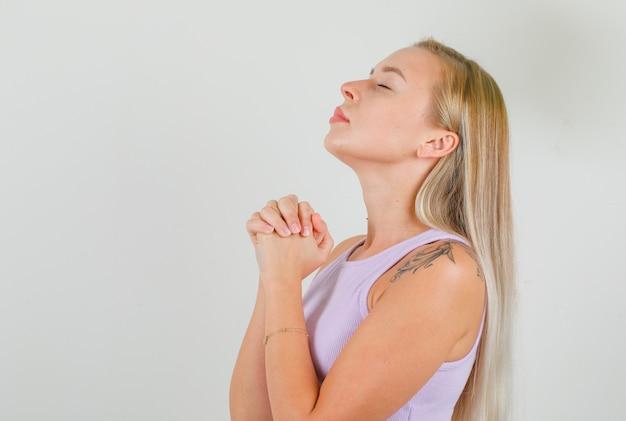 Młoda kobieta modli się z założonymi rękoma w podkoszulku i wygląda z nadzieją
