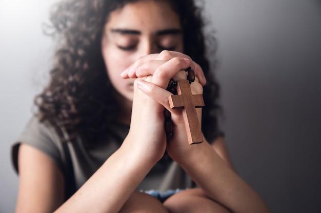 Młoda kobieta modli się ze świętym drewnianym krzyżem