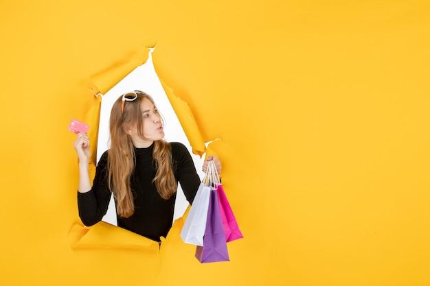 Młoda kobieta mody trzymająca torby na zakupy i kartę kredytową przez dziurę w rozdartym papierze w ścianie