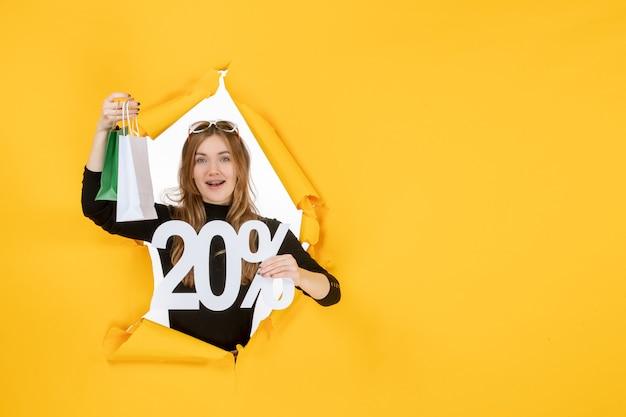 Młoda kobieta mody trzymająca torby na zakupy i procent zniżki przez rozdarty papierowy otwór w ścianie