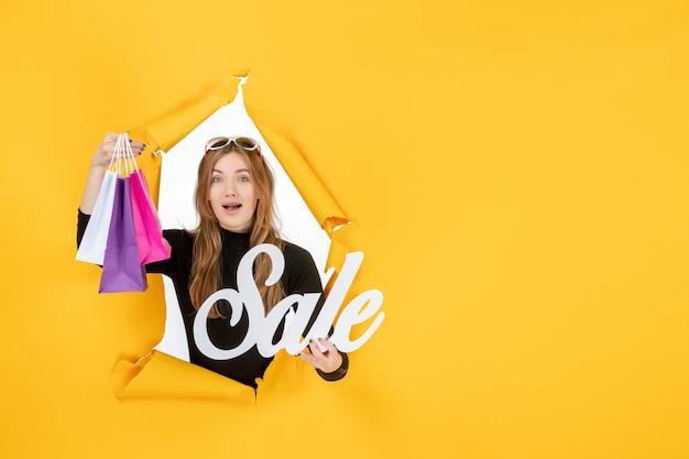 Młoda kobieta mody z torbami na zakupy przez rozdarty papierowy otwór w ścianie