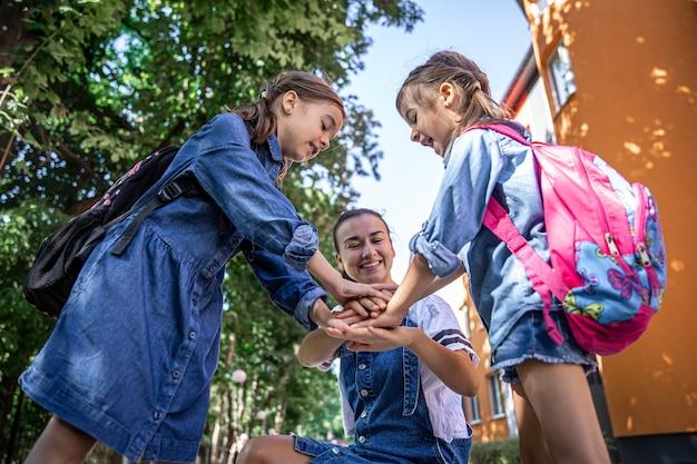Młoda kobieta moralnie wspiera córki trzymając się za ręce zachęca dzieci, mama towarzyszy uczniom do szkoły.