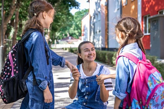 Młoda kobieta moralnie wspiera córki trzymając się za ręce, zachęca dzieci, towarzyszy uczniom do szkoły.