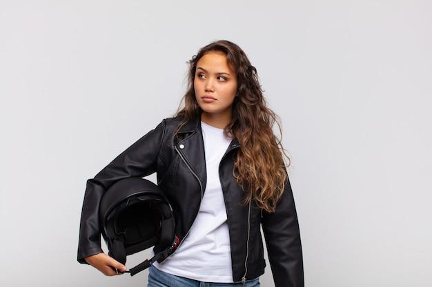 Młoda kobieta motocyklista czuje się smutna, zdenerwowana lub zła i patrzy w bok z negatywnym nastawieniem, marszczy brwi w niezgodzie