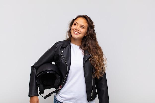 Młoda kobieta motocyklista uśmiecha się radośnie i marzy lub wątpi, patrząc w bok