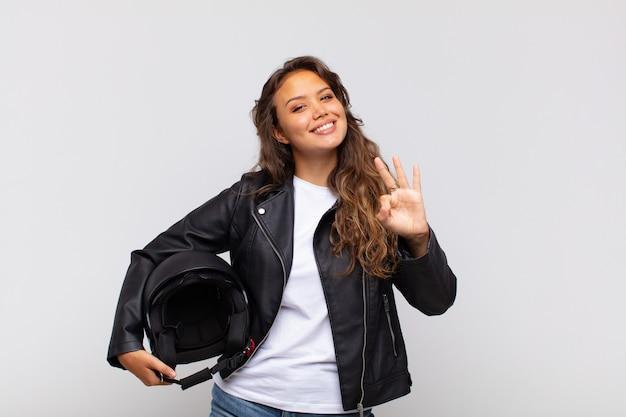 Młoda kobieta motocyklista uśmiechnięta i wyglądająca przyjaźnie, pokazująca numer trzy lub trzeci z ręką do przodu, odliczający