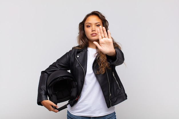 Młoda kobieta motocyklista wygląda poważnie, surowo, niezadowolony i zły, pokazując otwartą dłoń wykonujący gest stopu