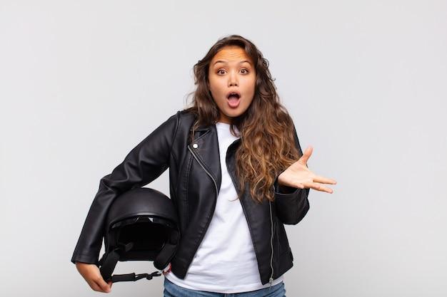 Młoda kobieta motocyklistka czuje się wyjątkowo zszokowana i zaskoczona, niespokojna i spanikowana, ze zestresowanym i przerażonym spojrzeniem