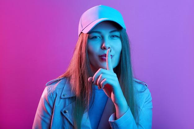 Młoda kobieta mówi cicho, woła o ciszę, pozuje z palcem na ustach gest shhh, stoi odizolowana nad różową neonową ścianą