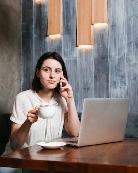 Młoda kobieta mówi przez telefon w biurze
