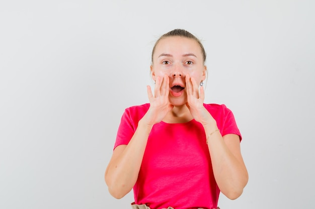 Młoda kobieta mówi sekret z rękami w pobliżu ust w t-shirt