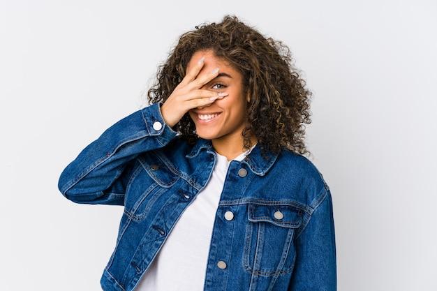 Młoda kobieta mruga do kamery palcami, zakłopotana zakrywająca twarz