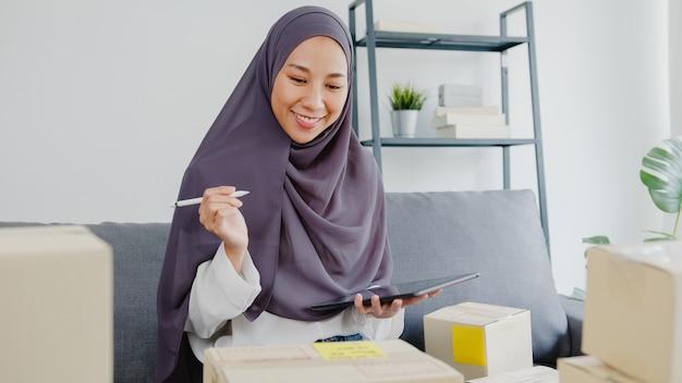 Młoda kobieta muzułmańska sprawdzić zamówienie zakupu produktu na magazynie i zapisać do pracy komputera typu tablet w domowym biurze.
