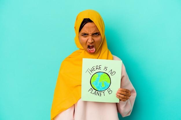 Młoda kobieta muzułmańska trzyma a nie ma tabliczki planety b na białym tle na niebieskim tle krzyczy bardzo zły i agresywny.
