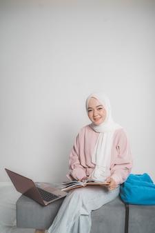 Młoda kobieta muzułmańska uśmiech podczas wysyłania wiadomości sms na telefon komórkowy na białym tle na białym tle