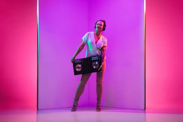 Młoda kobieta muzyk w słuchawkach wykonujących na fioletowym tle w świetle neonowym. pojęcie muzyki, hobby, festiwalu, rozrywki, emocji. radosny gospodarz imprezy, dj, portret artysty.