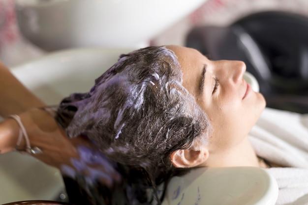 Młoda kobieta mycia włosów w salonie