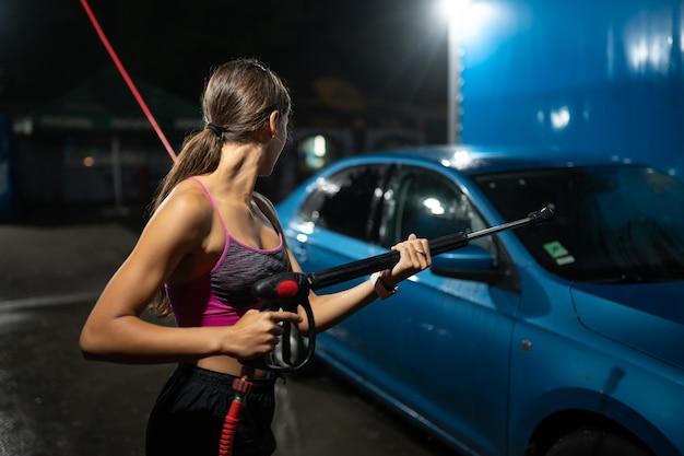 Młoda kobieta mycie niebieski samochód w myjni samochodowej