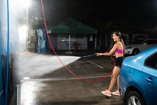 Młoda kobieta myje niebieski samochód na myjni samochodowej