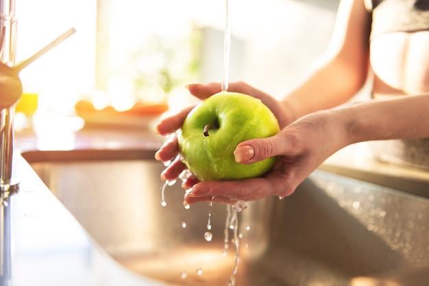 Młoda kobieta myje pod bieżącą wodą jabłko w oświetlonym słońcem zlewie kuchennym