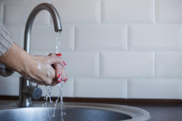 Młoda kobieta myje ręce mydłem, aby zapobiec zakażeniu koronawirusem